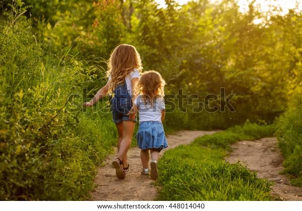 Zwei kleine Schwestern laufen an einem sonnigen Sommertag auf der Straße im Park. Familienzeit. Kluge Babys.