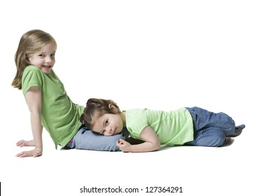 Two little sisters sitting and lying on the ground over white background