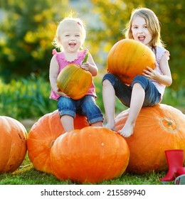 Two little sisters sitting on huge pumpkins on a pumpkin patch