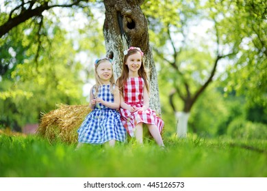Two little sisters sitting on a haystack in apple tree garden on warm and sunny summer day