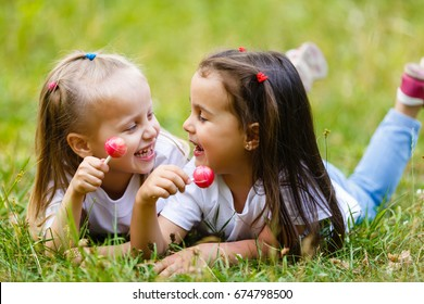 Two little smiling girls lying on the grass in the park. eat candy