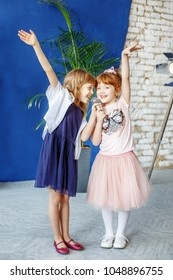 Two little smiling kids dance and sing a song in karaoke. The concept is childhood, lifestyle, music, singing, friendship.