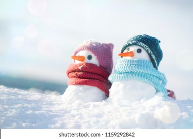 Two little snowmen the girl and the boy in knitted caps and scarfs on snow  in 0b3370876bd6