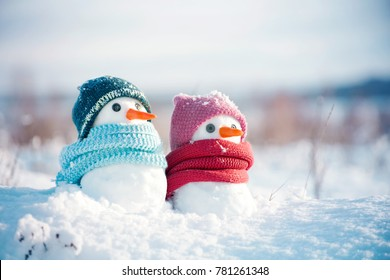 Two little snowmen the girl and the boy in knitted caps and scarfs on snow in the winter. Festive background with a lovely snowman. Christmas card, copy space