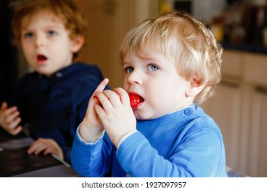 Two little toddler boys, cute brother children watching cartoons on tv and eating lolipop candy. Happy siblings together in daycare or nursery, having lunch.
