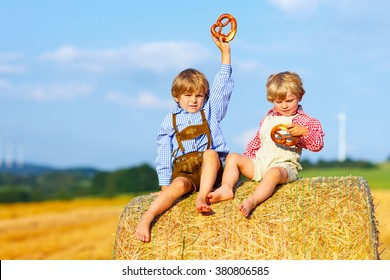 Two little twin kids boys sitting on hay stack or bale and speaking on yellow wheat field in summer. Children having fun together and eating traditional pretzel