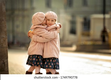 Two little twin sisters are hugging on a city street. One girl gently kisses another. Image with selective focus and toning.