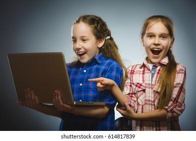 Two little wondering girls using laptop isolated grey background