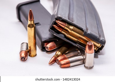 Two loaded magazines, one for a 223 caliber rifle and the other for a 9mm pistol along with additional bullets for each on a white background