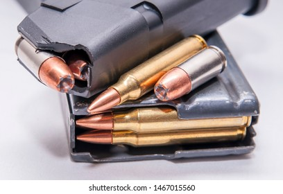 Two loaded magazines, one for a 9mm pistol and the other for a 223 caliber rifle on a white background