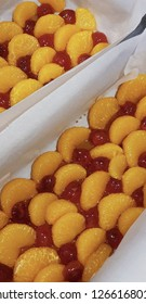 Two loaf cake tins with mandarin slices and cherries arranged ready for cake batter to be poured on top to make upside-down cake.