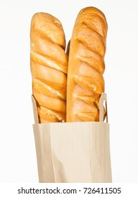 Two loaves bread in a brown paper bag on white background