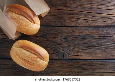 Two loaves of small white bread on wooden background, top view with copy space