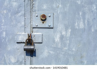 Two locks (mortise and hinged) on a closed steel garage door with an inaccurately painted tassel in gray.