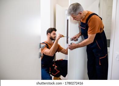 Two locksmith, repairmen, workers in uniform installing, working with house door lock using screwdriver. Repair, door lock service concept. Selective focus on young man. Horizontal shot