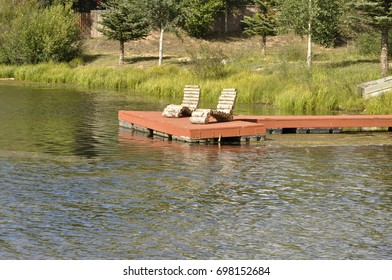 two log chairs on a red deck by a small pond