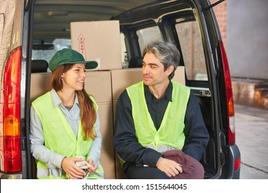 Two logistics workers as a team of transporters with vans take a break