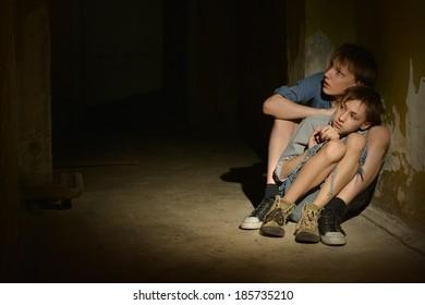Two lonely boys sitting in a dark cellar