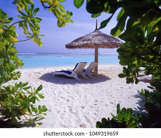 Two long chairs, beach umbrella near the ocean on a tropical white sand beach