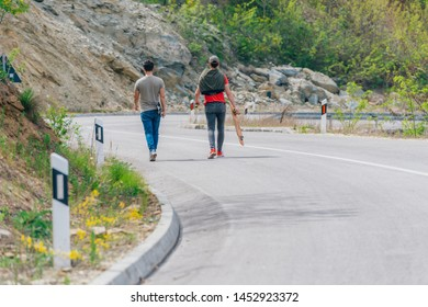 Two longboarders holding their longboards and walking downhill while chatting with eachother.