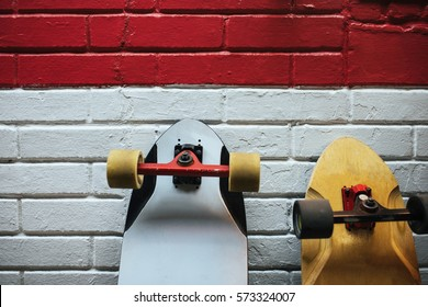 Two longboards at the brick wall