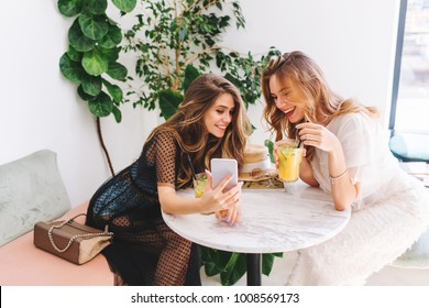 Two long-haired girls resting in cafe with modern interior and laughing. Indoor portrait of funny smiling ladies in trendy clothes making selfie while drink fruit cocktails.