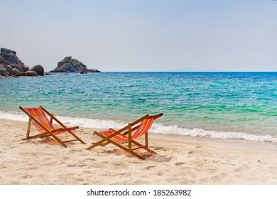 Two lounge chairs on the bay beach with rocks on the background