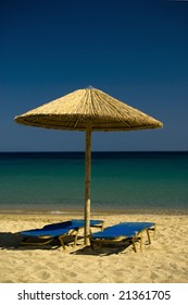 Two lounge chairs and umbrella  on Paradise Beach , Mikonos , Greece.