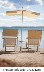 two lounge chairs and umbrella on beach