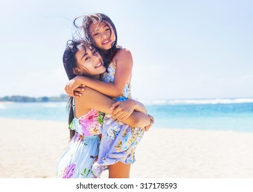 two lovely asian sisters on a beach