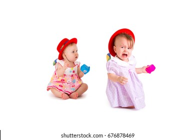 Two lovely babes in colored dresses and red hats are playing on a white background