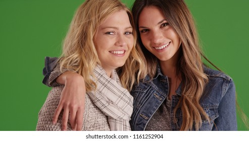 Two lovely female friends embracing posing for camera on green screen