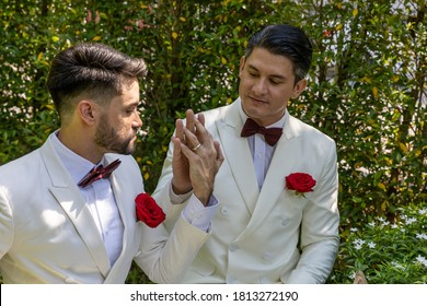 Two lovely gay are exchange their rings during wedding ceremony in a garden at home with happiness