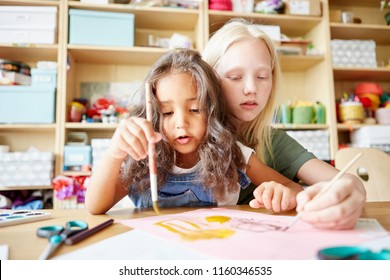Two lovely girls painting cute picture together while attending art class in school