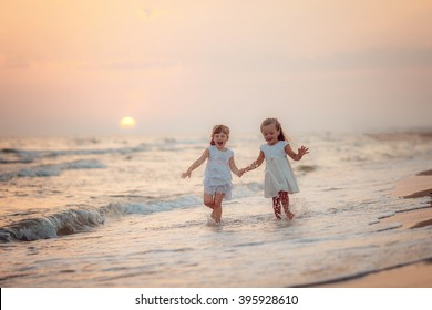 two lovely girls in white dresses walking on the beach at sunset