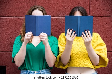 Two lovely hipster woman are standing against a red wall with books in their hands. Fashion conception.