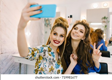 Two lovely smiled young women having fun, making selfie on phone in hairdresser salon. Smiling, expressing positivity, happiness, stylish look, fashionable models, luxury makeup, coiffure