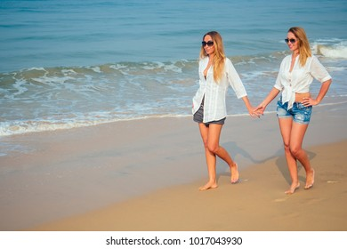 two lovers and beautiful women are walking on the beach holding hands