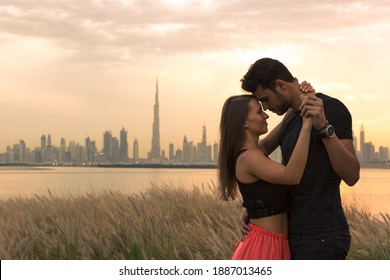 Two lovers dancing and embracing during sunset with city skyline view background. Romantic setting.