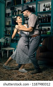 Two lovers dancing tango style in a vintage coffee room.