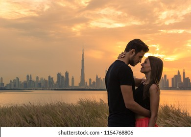 Two lovers embracing during sunset. City view background.