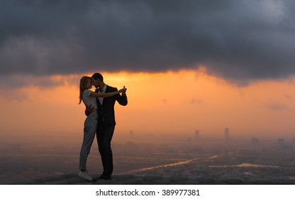 Two lovers embracing/dancing on top of a skyscraper overlooking the city at sunrise/sunset. Romantic setting.