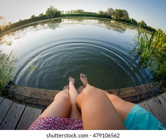 Two lovers hanging their legs at the riverside- with fish eye lens