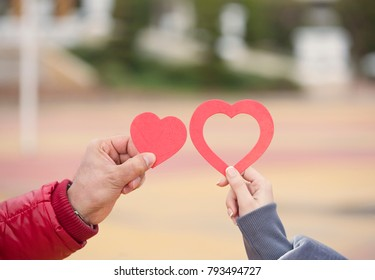 Two lovers holding paper heart