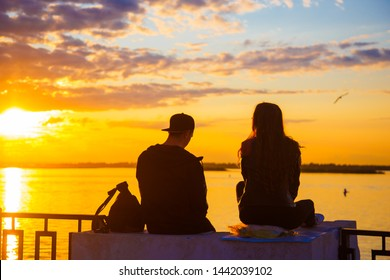 The two lovers looked out at the water during sunset. The concept of travel. Happy couple of lovers relaxing on the sea pier under sunset sun light at evening time.