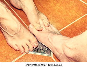 Two lovers, man and woman barefoot in shower.  Feet on red tilles selective focus on toes