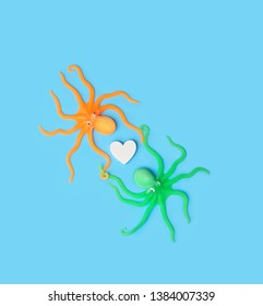 two lovers octopus toys and heart on blue background. Colorful sea animals isolated on blue background, small cute octopus. creative concept. top view, copy space