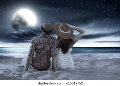 Two lovers on beach at night and landscape of sea with sky and moon