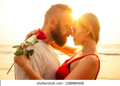 two lovers people at sunset by the sea romance and tenderness feelings first love date.man and woman blonde in a dress on the beach with a rose sun rays.Valentine's day and International Women's Day