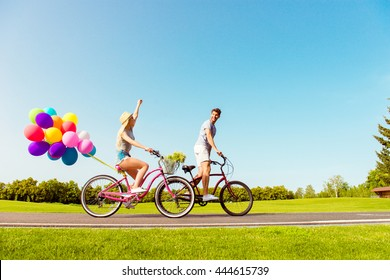 Two lovers riding bicycles with balloons on the background of sky